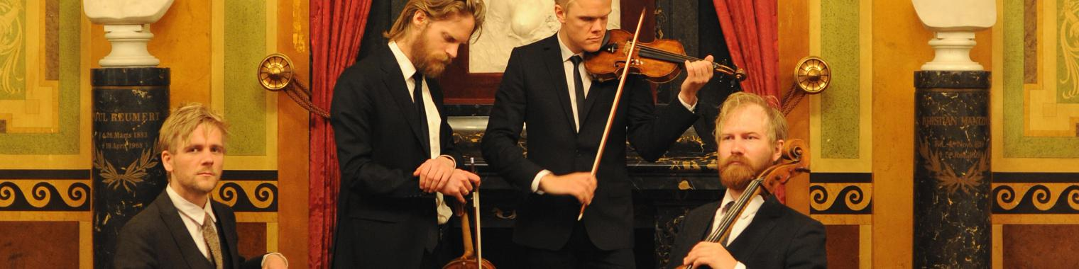 The Danish String Quartet with instruments in an opulently decorated room