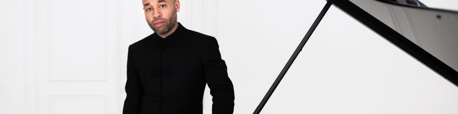 Aaron Diehl wearing all black standing next to open grand piano