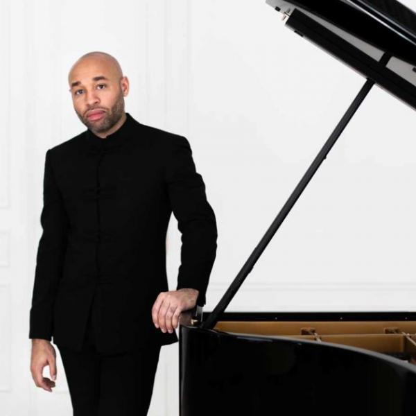 Aaron Diehl standing next to grand piano