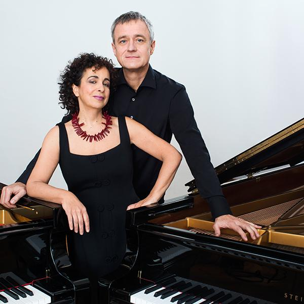 Duo Tal and Groethuysen standing between two grand pianos