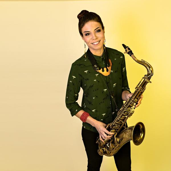 Melissa Aldana holding saxophone and standing in front of yellow background