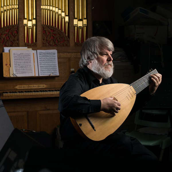 Paul O'Dette playing the lute in front of a pipe organ