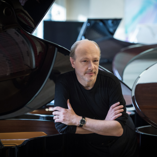 Marc-André Hamelin wearing a black sweater and leaning on a gran piano when many open grand pianos behind him