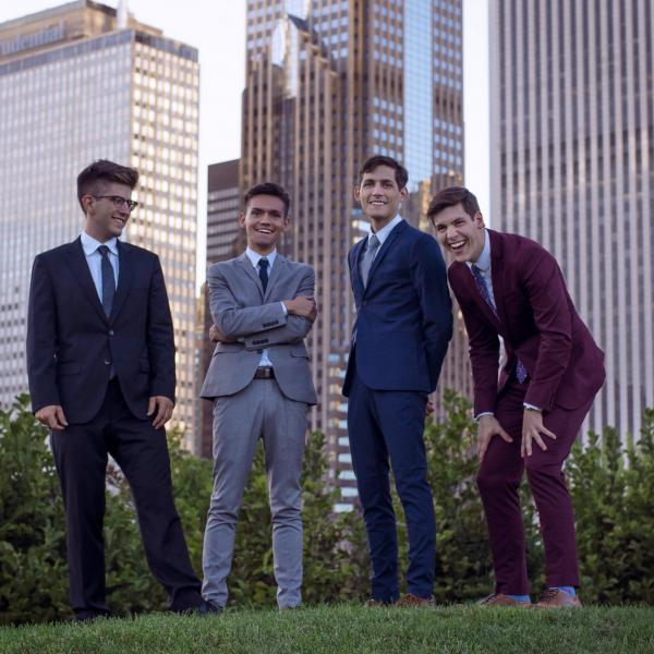 The members of NOIS saxophone quartet pose for a photo in Chicago's Grant Park with high rise buildings in the background