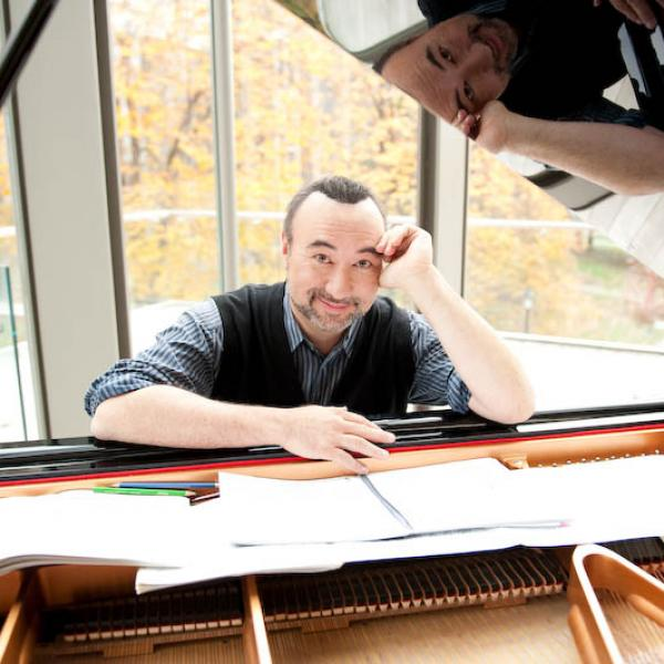 Jon Kimura Parker seen through the lid of an open piano leaning over sheet music splayed across the piano strings