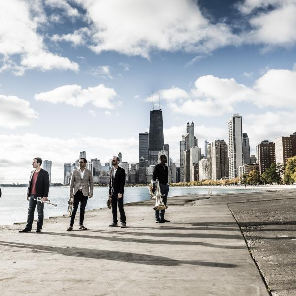 Axiom Brass standing with instruments outside, with the Chicago skyline in the background
