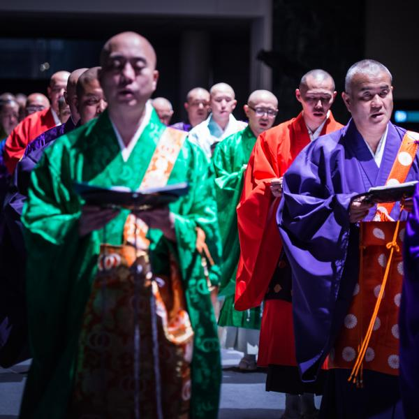 Shomyo no Kai – a group of men wearing brightly colored silk robes and standing in two lines chant while holding open books