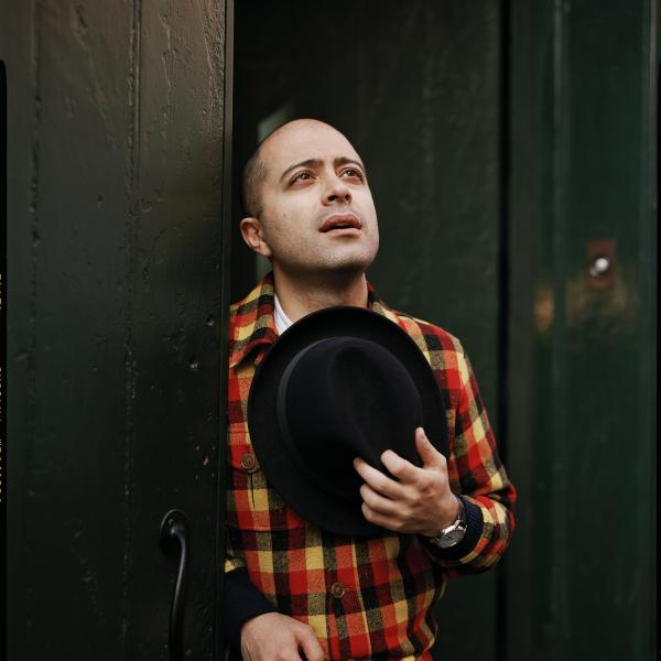 Mahan Esfahani shown wearing a red, brown, and yellow plaid jacket and holding brown hat to his chest