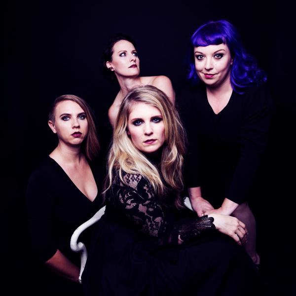 Quince vocal ensemble: 4 women in black, with a black background, crowd close to the camera