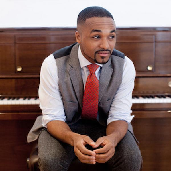 Sullivan Fortner sitting in front of a brown upright piano, wearing a grey vest and pants, white shirt, and red tie