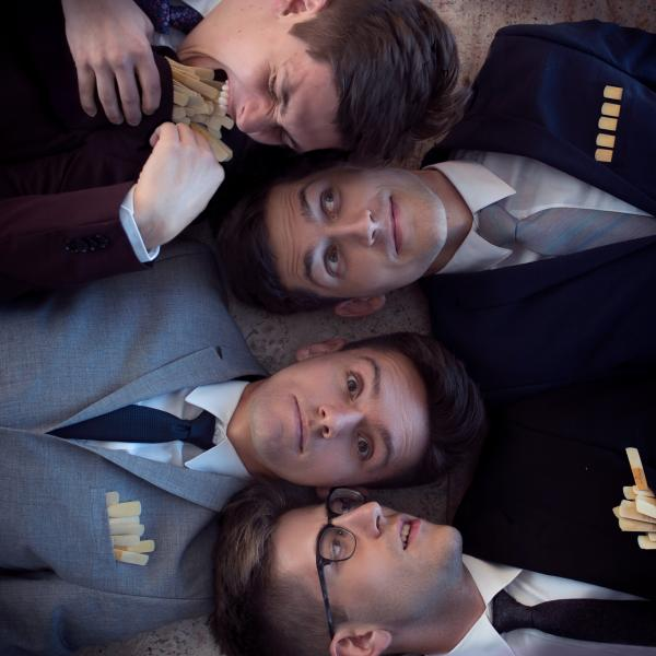 ~Nois saxophone quartet laying with their heads next to each other. The two in the middle, Brandon Quarles and Janos Csontos, face the camera. Jordan Lulloff on the bottom turns his head to the middle two, and Hunter Bockes, top, tries to bite a pocketful of saxophone reeds.