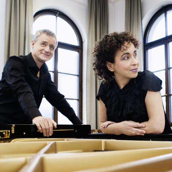 Piano duo Yaara Tal and Andreas Groethuysen lean over a piano