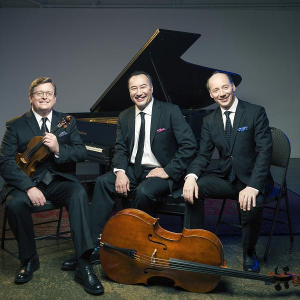 The Montrose Trio sitting with instruments in front of a piano