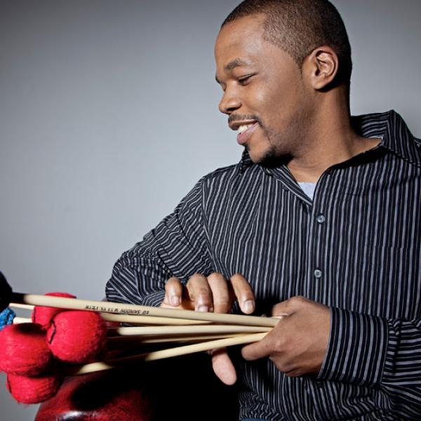 Warren Wolf holding a bundle of vibraphone mallets
