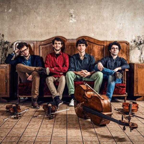 Vision String Quartet sitting on a vintage sofa with instruments in front of them