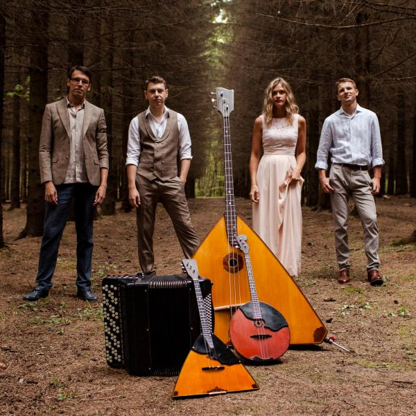 Russian Renaissance standing in the woods behind a pile of their instruments