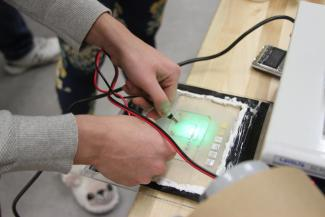 A person using tools on an circuit board.