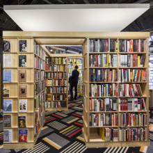 A male student stands amongst several shelves of books in a bookstore.