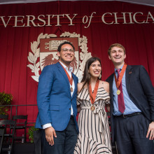 Three students pose on stage in front of the UChicago seal wearing medals.