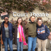 A group of four students post in front of an ivy-covered wall in front of the Court Theatre.