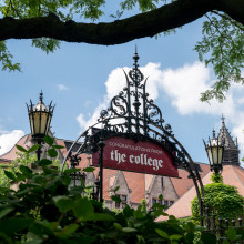 A banner that reads 'Congratulations from the College' is shown hanging from a large metal gate with bushes and trees in the foreground