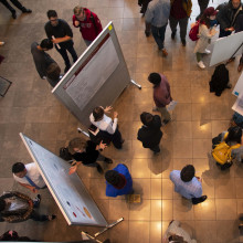 An aerial shot of a group of students presenting posters at an undergraduate research symposium.