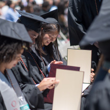 A row of seated students in cap and gowns look at their diplomas.
