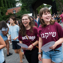 Two smiling female students walk amongst a group of students wearing maroon UChicago shirts in English and Hebrew.