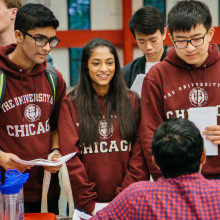 Two male students and a female student wearing UChicago maroon sweatshirts ask a male at a table a question.
