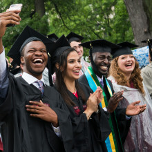 A group of students wearing caps and gowns clap and cheer, while one takes a selfie with a cell phone.