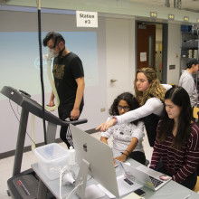 A female teaching assistant points out something on a computer screen to two female students while a male student walks on a treadmill in a lab class.