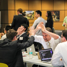 A group of three male students around a table high five.