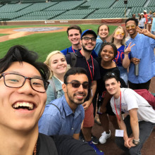 A group of students take a group selfie at the edge of the field of a baseball stadium.