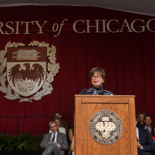Valerie Jarrett stands behind a podium on a stage draped with red curtains and University of Chicago seal.