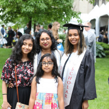 A family poses with their student wearing a graduation cap and gown.