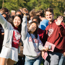 A group of students in UChicago gear grin and wave on a sunny summer day.