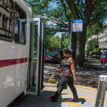 A person steps aboard a campus shuttle bus in summer.