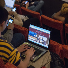 A student sits in an auditorium with a laptop on his lap.