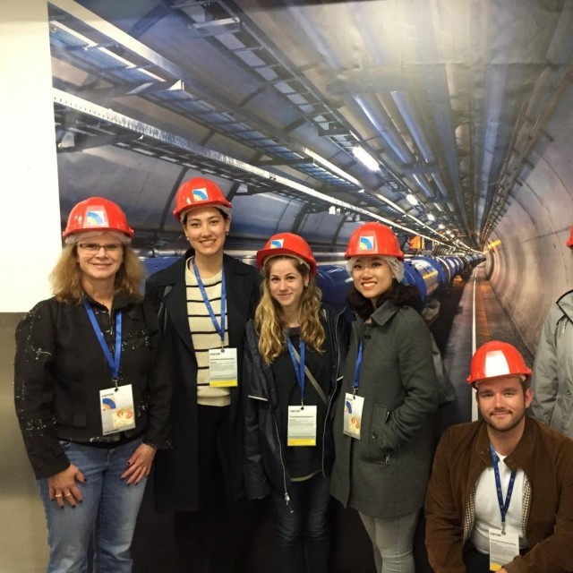 A group of students in hard hats stand in front of a post at the European Center for Nuclear Research in Switzerland.