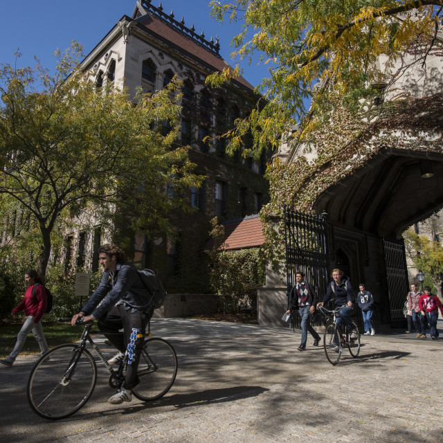 A student walks outside on a fall day while two cyclists ride through a leaf-covered archway on the UChicago campus.