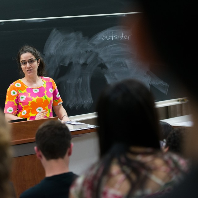 A female instructor stands in front of a blackboard while teaching a lecture class.