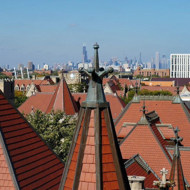 The city of Chicago is seen behind the red rooftops of UChicago's gothic buildings.
