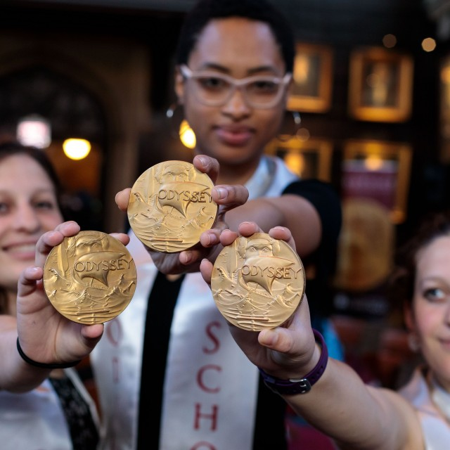 """Three students wearing """"Odyssey Scholarship"""" ribbons around their necks pose with gold scholarship medals."""