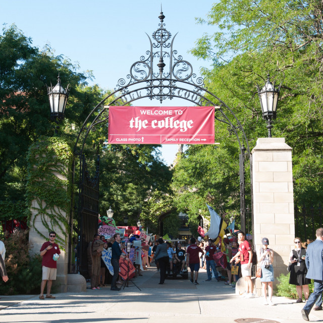 "A crowd walks under an archway with a sign hanging that says ""Welcome to the College"""