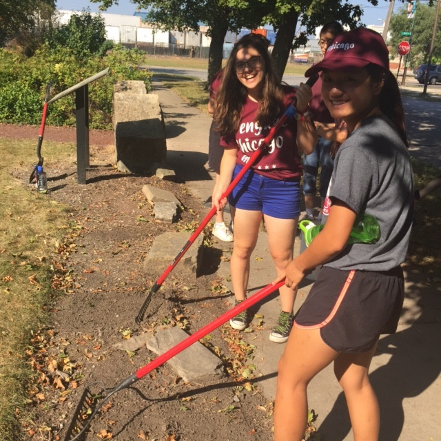 Two students stand with shovels while doing work in a community garden.