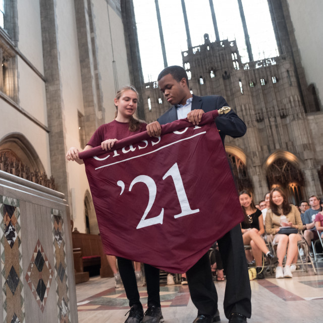 Two students unroll a maroon flag that says 'Class of '21'