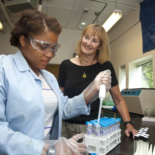 A student puts specimens into test tubes in a lab while a faculty member looks on.