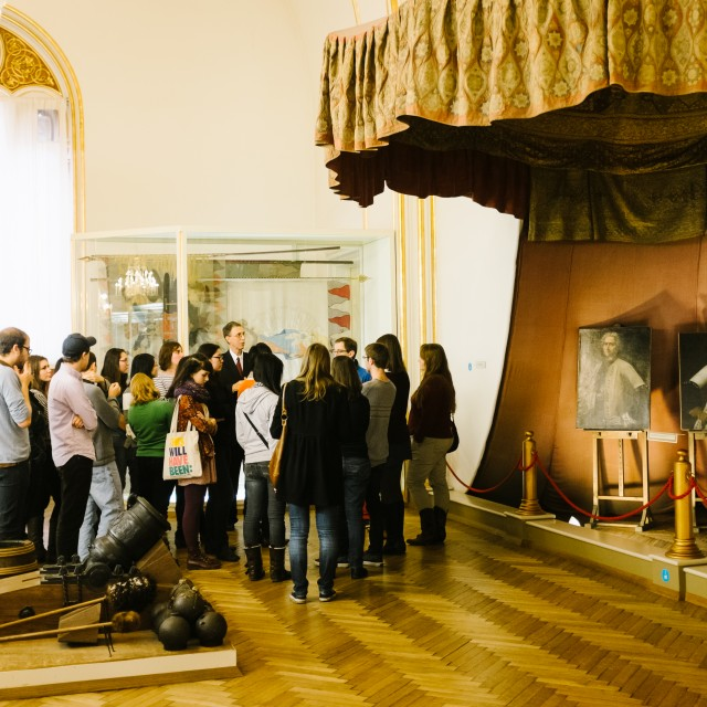 A group of students stand around a professor as he discusses an exhibit in a museum in Vienna.