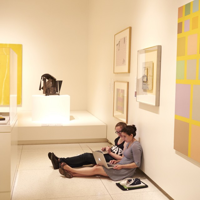 Two female-presenting students with laptops sit on the floor of an art gallery, their backs to the wall and legs outstretched.