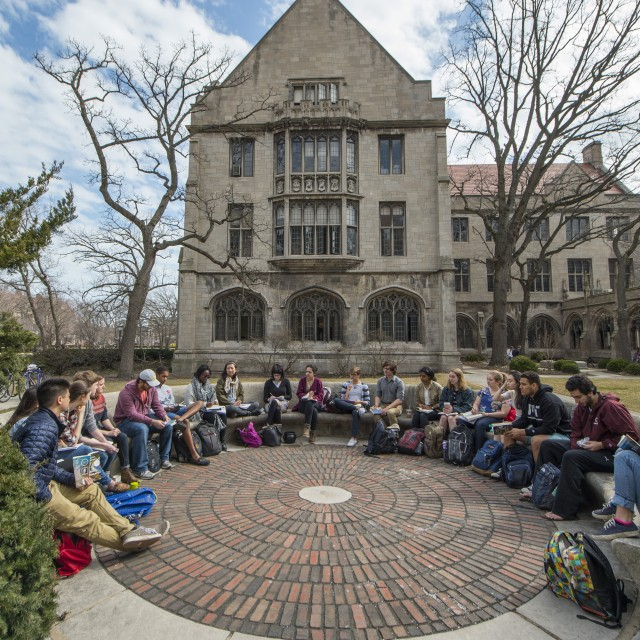 A class of students sits on a semi-circular stone bench on a cool day in fall, with leafless trees and a stone building framed behind the group.